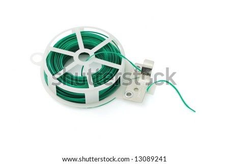 Twist ties in spool and cutter on white background - stock photo