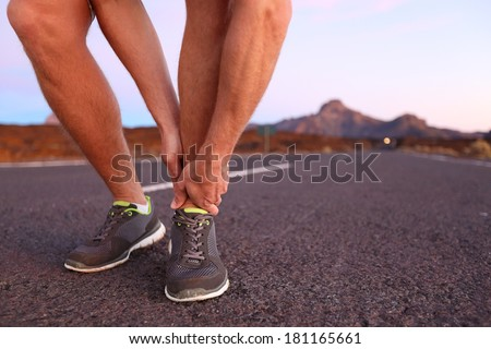 Twisted angle - running sport injury. Male athlete runner touching foot in pain due to sprained ankle. - stock photo