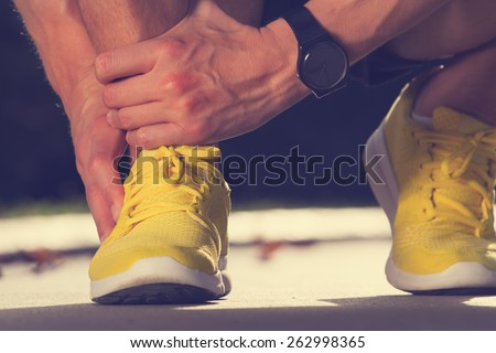 Twisted ankle while jogging. Warp up before any exercise. - stock photo