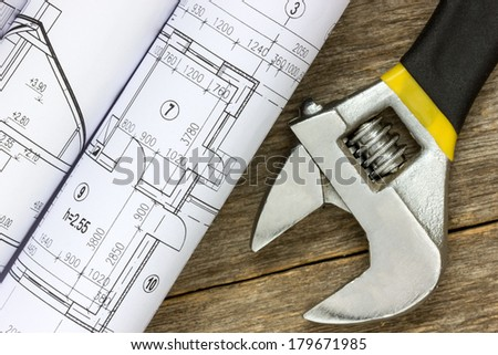 Twisted technical drawing and adjustable wrench on the wood background