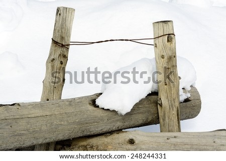 Twisted wire holds fence posts together in winter - stock photo