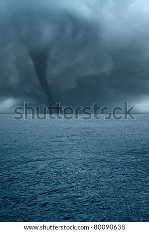 twister with dark clouds on the ocean - stock photo