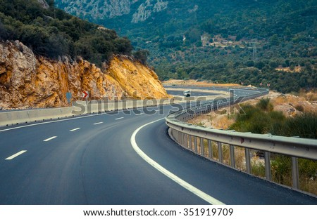 Twisty road between mountain hills - natural landscape with curves of asphalt road for auto transport. Mountainous terrain with winding highway lines. - stock photo
