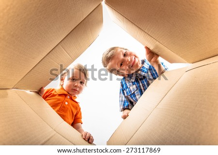 Two a little boys opening cardboard box and looking inside with surprise. - stock photo