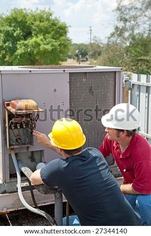 Two AC technicians on a roof repairing an industrial compressor unit. - stock photo