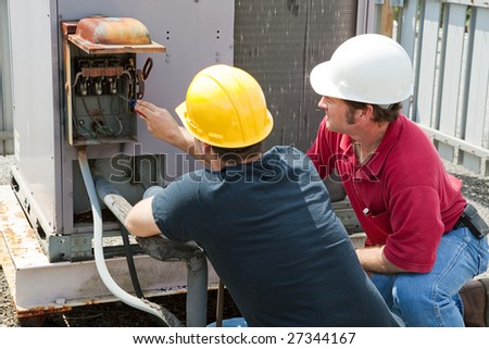 Two AC technicians repairing an industrial air conditioning compressor. - stock photo