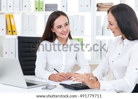 Two accountants talking and working together in their white office. Concept of collaboration and friendly relationships
