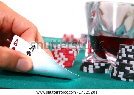 Two Aces A hand is showing two aces on a poker table with a glass of red liquor. Isolated over white.