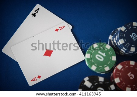 Two aces and gambling chips on casino table - stock photo