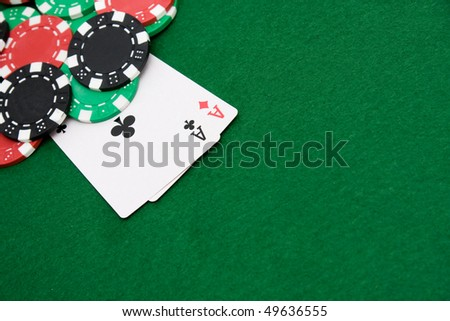 Two aces and gambling chips on green casino felt background - stock photo
