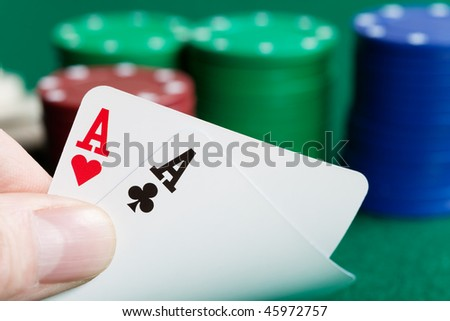 Two aces in a poker hand with chips in the background