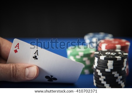Two aces in hand and Gambling chips on casino blue felt - stock photo