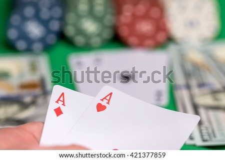 two aces in hand with poker card, chips  and money