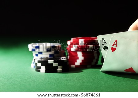 two aces on green table with chips and black background - stock photo
