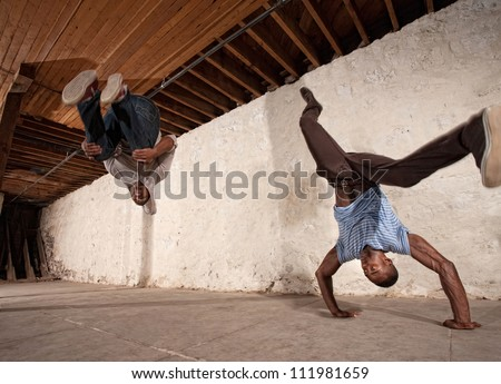 Two acrobatic capoeria artists do headstands and backflips - stock photo