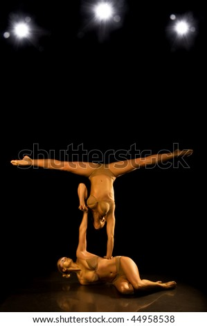Two acrobatic girl toned in gold - stock photo