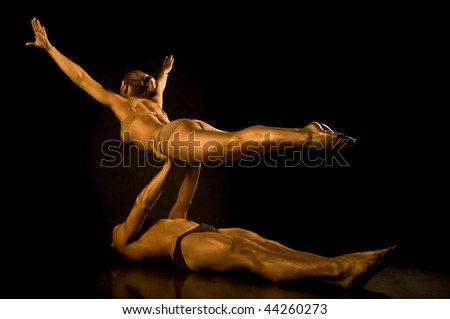 Two acrobats toned in gold - stock photo