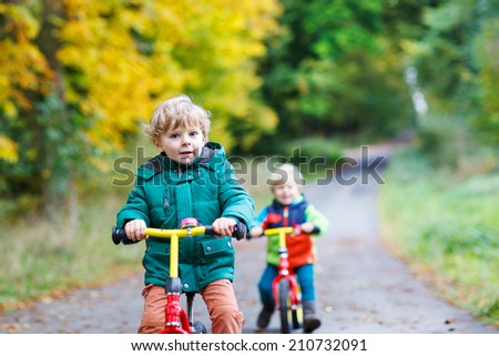 Two active brother boys driving fast on bikes in autumn forest. Selective focus - stock photo