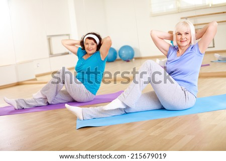 Two active females doing physical exercise in sport gym  - stock photo