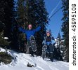 Two active seniors in an alpine setting enjoying the sun. They wear snowshoes and have ski poles. - stock photo