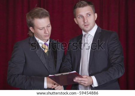 two actors with clipboard discussing on the stage
