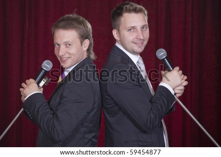 two actors with microphones playing spectacular on stage - stock photo