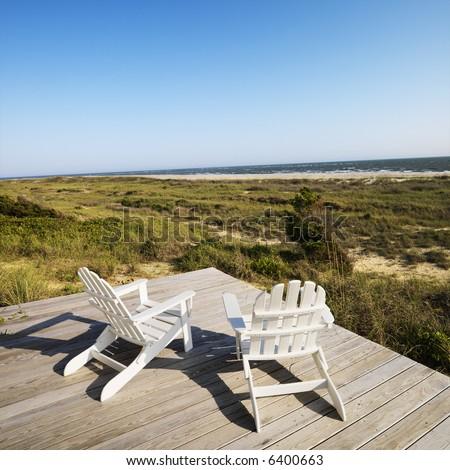 Two adirondack chairs on wooden deck overlooking beach at Bald Head Island, North Carolina. - stock photo