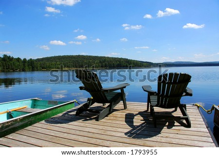 Two adirondack wooden chairs on dock facing a blue lake with clouds reflections - stock photo