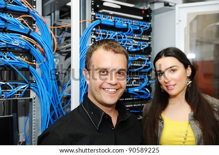 Two administrators, male and female, at server room - stock photo