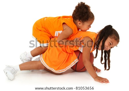 Two adorable african-hispanic girls playing basketball in uniform. Clipping path over white. - stock photo
