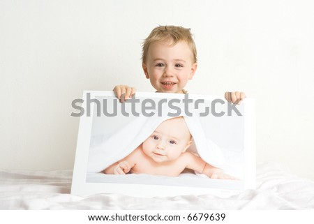 Two adorable blond little boys; one is two years old, the other is infant. Unclear whether image of infant is photo or illusion to look like photo. one and the same boy (yearling,two years old)