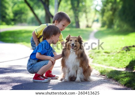 Two adorable boys, brothers, caressing cute dog in the park, summertime, enjoying the day - stock photo