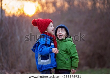 Two adorable boys, brothers, on a winter day, sunset time, smiling and having fun - stock photo