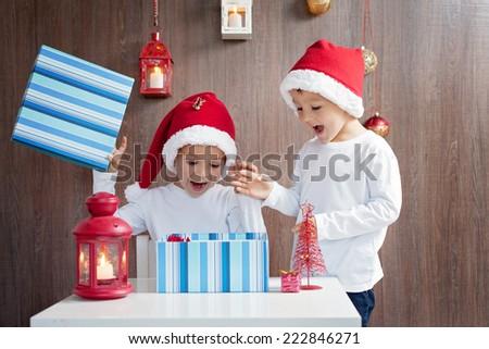 Two adorable boys, opening presents on Christmas - stock photo