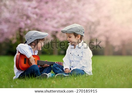 Two adorable caucasian boys in a blooming cherry tree garden, playing guitar in the afternoon - stock photo