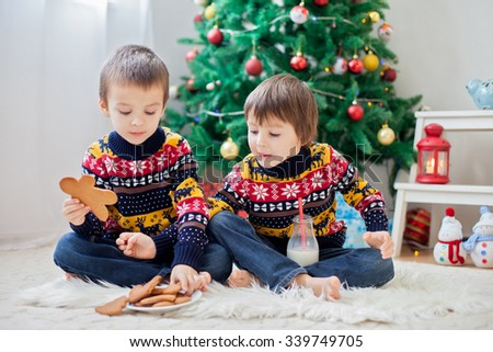 Two adorable children, boy brothers, eating cookies and drinking milk at home, Christmas decoration behind then, kids having fun. Christmas concept - stock photo