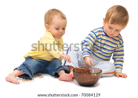 Two adorable children playing with buckwheat. Isolated on white - stock photo