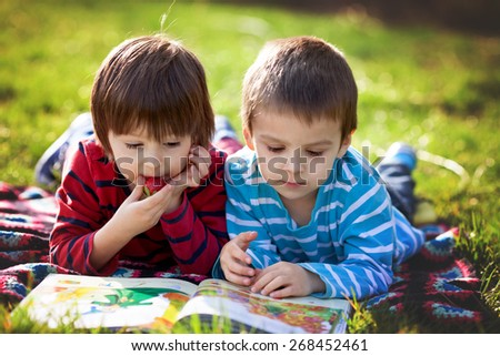 Two adorable cute caucasian boys, lying in the park in a fine sunny afternoon, reading a book and eating strawberries, educating themselves and having fun - stock photo