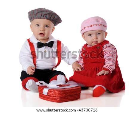 Two adorable dressed-up babies celebrating Valentine's Day.  She gives a skeptical eye as he holds her hand.  Isolated on white. - stock photo