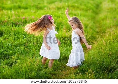 Two adorable girl in white dresses dancing on the meadow - stock photo