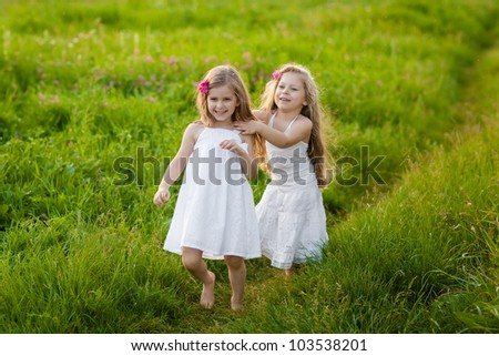 Two adorable girl in white dresses running on the meadow - stock photo