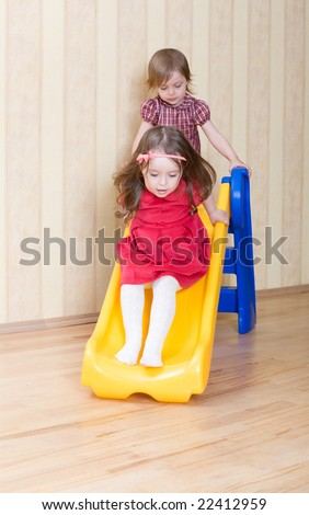 Two adorable girls having fun atop playground slide at living room - stock photo