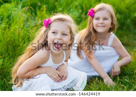 Two adorable girls in white dresses playing on the meadow - stock photo