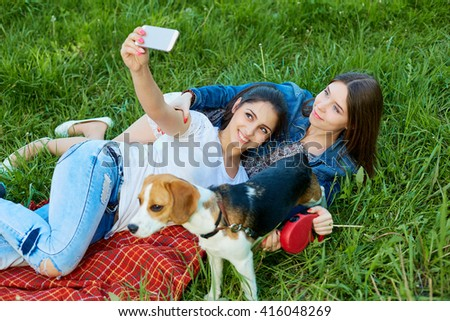 Two adorable girls posing with their dog   in park. - stock photo