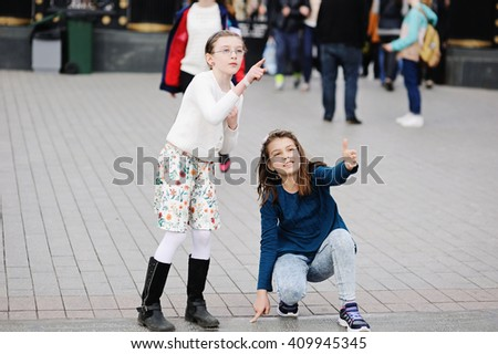Two adorable girls walking and having fun on the spring city streets. Moscow. Russia
