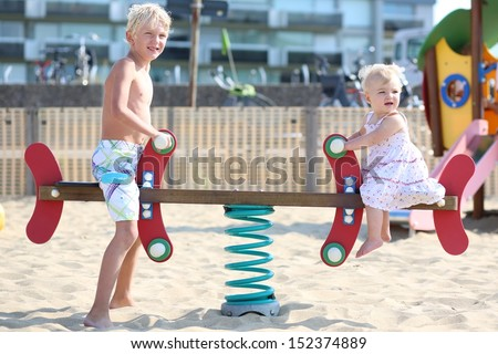 Two adorable happy blond kids, teenager boy and his little baby sister, playing together at outdoors sandy beach playground rocking on a spring seesaw swing - stock photo