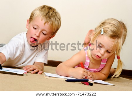two adorable happy children drawing with crayons at playschool