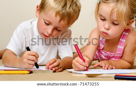 two adorable happy children drawing with crayons at playschool - stock photo