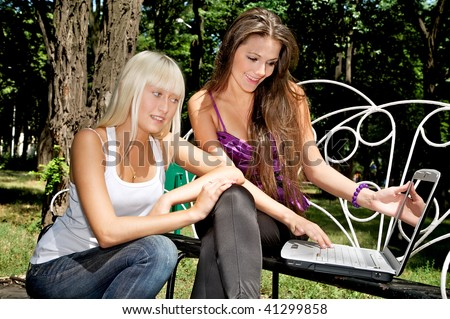 Two adorable happy girls with the computer on a white bench in green park