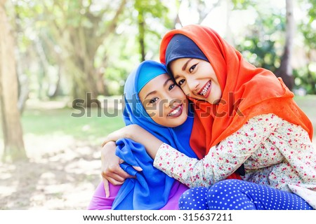 two adorable indonesian muslim sisters - stock photo
